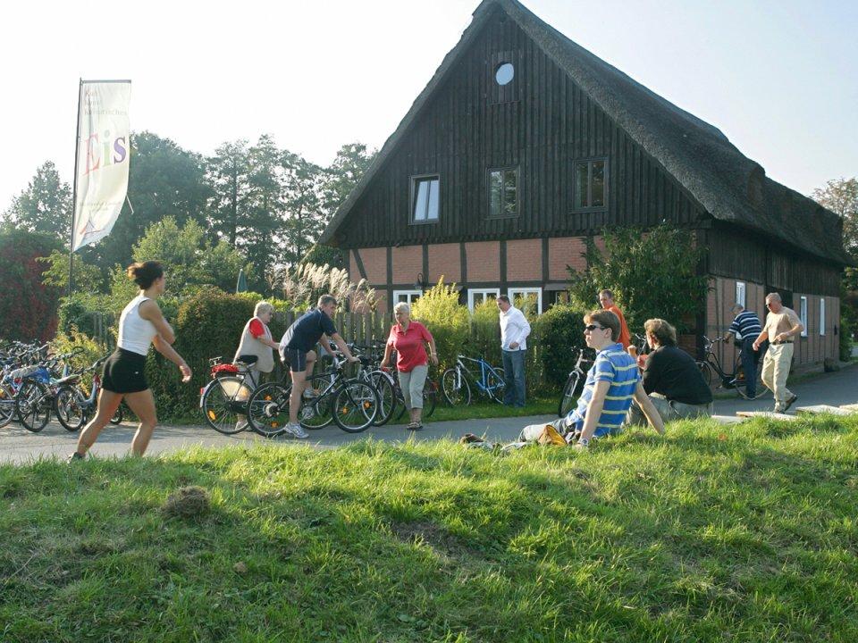 Strecke am Wümmedeich mit Radfahrern, Skatern und Rastenden an einem Fachwerkhaus