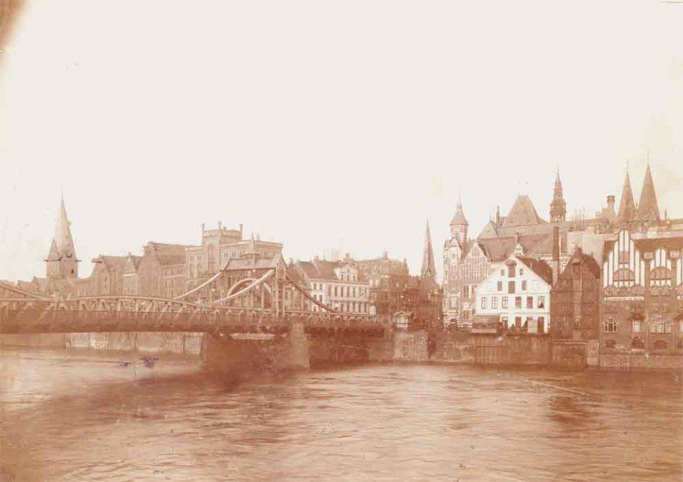 Die Schwarzweißfotografie zeigt eine Brücke über einen Fluss mit großen Speichern am gegenüberliegenden Ufer.