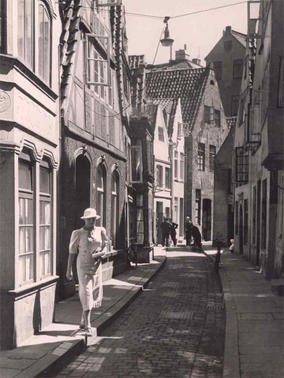 Diese Schwarzweißfotografie zeigt, wie eine Frau in weiß eine schmale Straße überquert, die von Häusern eng bebaut ist.