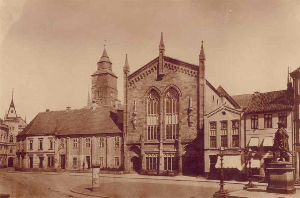 Auf der rechten Bildseite eine Statue, links davon ein langer Platz. Geradeaus geht der Blick auf ein großes historisches Gebäude. Hierbei handelt es sich um ein Schwarzweißfotografie.