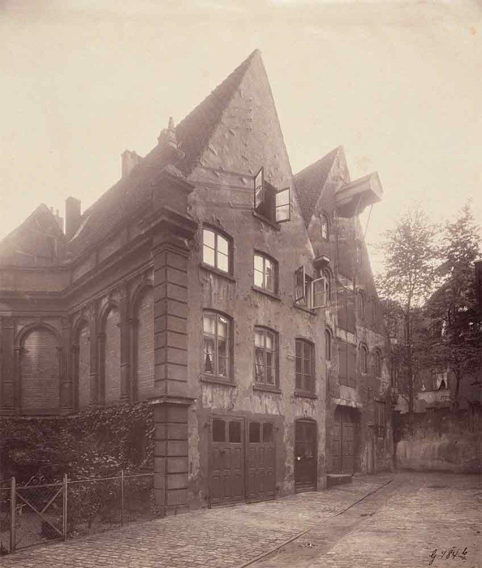 Zwei vierstöckige Häuser mit auffällig spitz zulaufenden Dächern in schwarzweiß fotografiert.