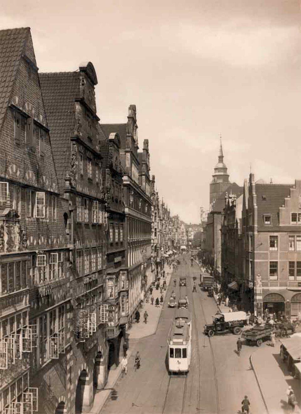 Eine belebte Straße mit historischen Gebäuden und einer Straßenbahn im Jahre 1929, schwarzweiß fotografiert.