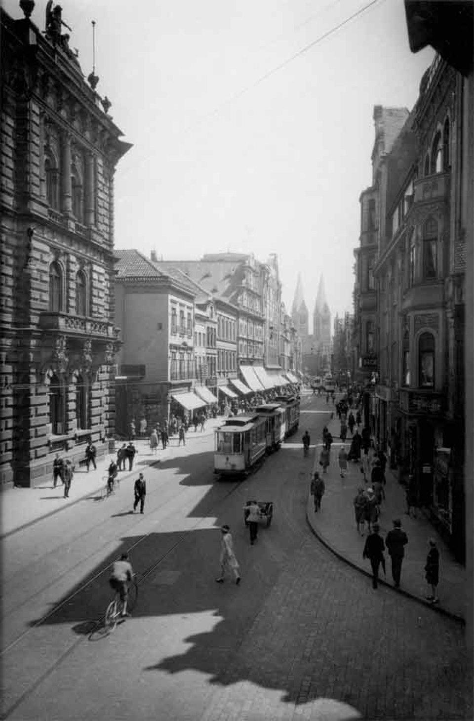 Eine schwarzweiß- Aufnahme zeigt eine Straße mit Menschen und einer Straßenbahn. Am Ende stehen zwei Türme eines Domes.