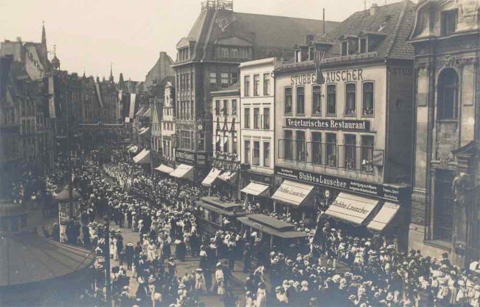 Eine Schwarzweißfotografie einer menschengefüllten Straße. In der Mitte ist ein Festzug zu sehen.
