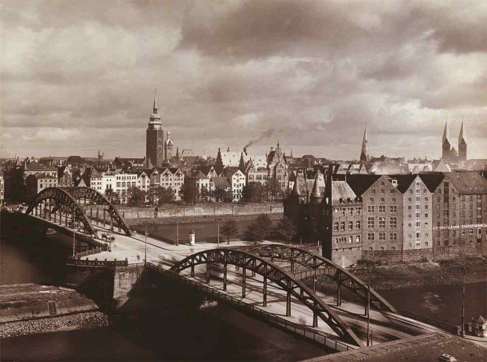 Eine Bogenbrücke, die zwischendurch von einer Landzunge unterbrochen wird. Diese Fotografie stammt aus dem Jahre 1928 und ist schwarzweiß.