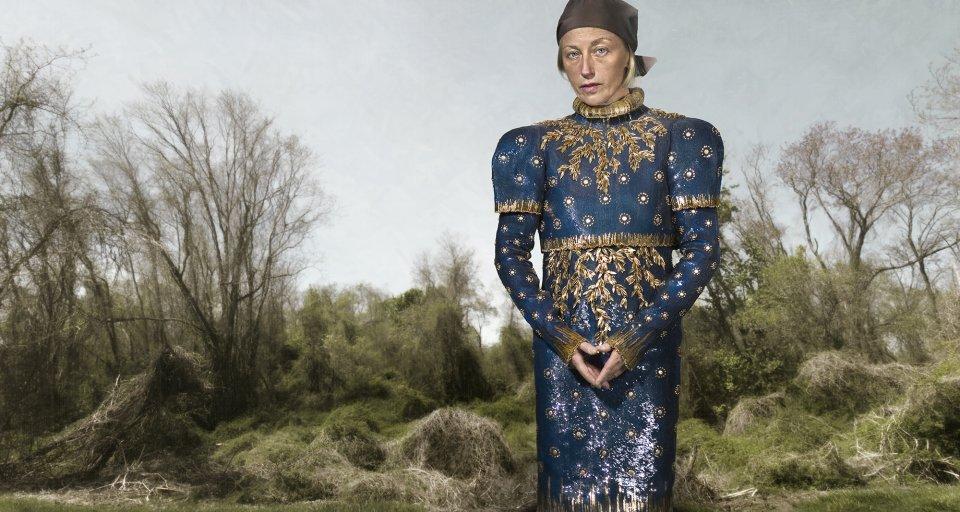 Eine blonde Frau steht vor einem bewachsenen Wald in einer blau, goldenen Robe mit Kopftuch und faltet ihre Hände vor sich zusammen.