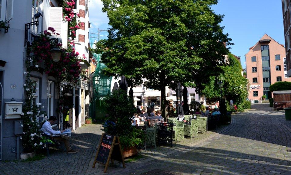 Kleines Gässchen mit grünen Bäumen und Menschen in einem Café