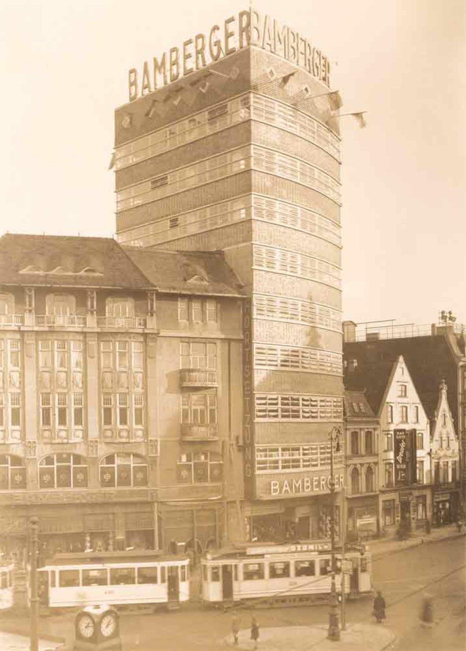 Ein hohes Kaufhaus zwischen kleineren Gebäuden. Im Vordergrund fährt eine Straßenbahn. Eine Schwarzweißfotografie von 1930.