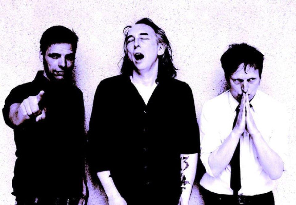 3 Männer stehen nebeneinander, eine zeigt mit ausgestrecktem Arm nach vorne. Das Foto ist schwarz/weiß/lila.