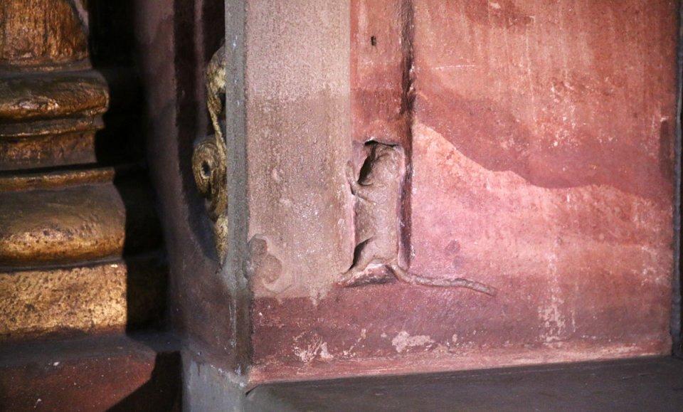 Eine kleine, in Stein geschlagene Maus am Fuße eines Portals im Dom.