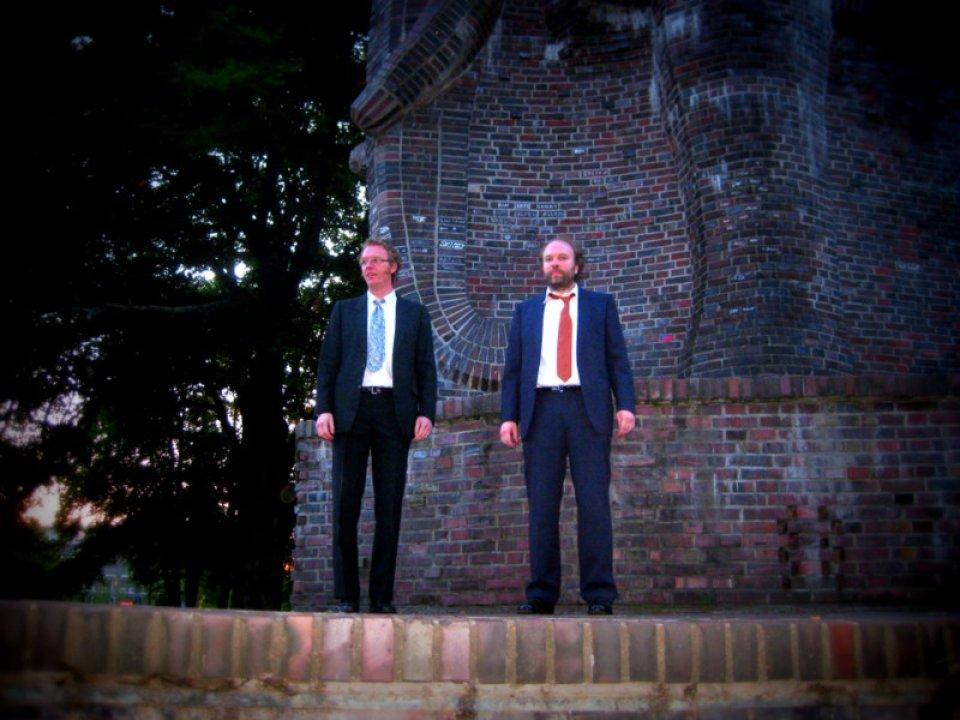 2 Männer in Anzügen stehen vor einer Elefanten-Statue aus Stein