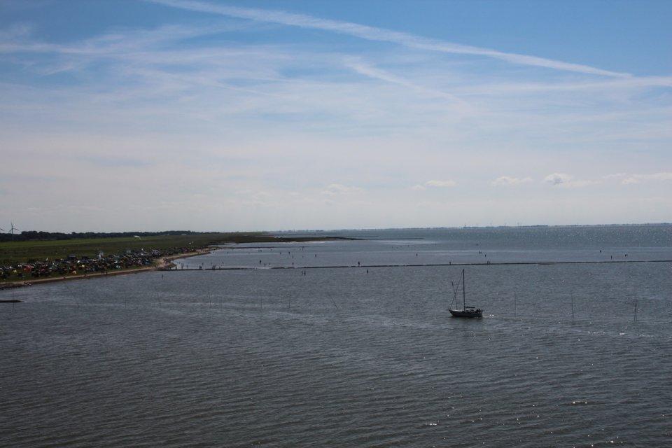 Zu sehen ist das Meer mit einer angrenzenden Wiese. Auf dem Meer ist ein kleines Schiff zu erkennen.