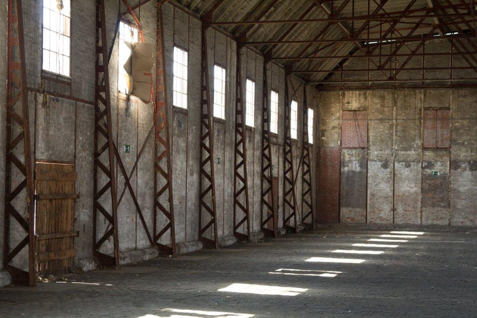 Blick in eine Linse in eine leere Fabrikhalle.