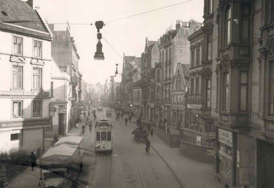 Diese Schwarzweißfotografie zeigt eine von Häusern gesäumte Straße, auf der ein LKW und eine Straßenbahn fährt. Einige Fahrradfahrer und Fußgänger beleben die Straße.