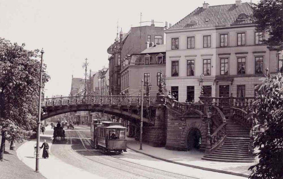 Die Schwarzweißfotografie einer Brücke, unter der eine Straße entlang führt. Eine Straßenbahn und eine Kutsche fahren unter ihr hindurch. Im Hintergrund stehen Häuser.