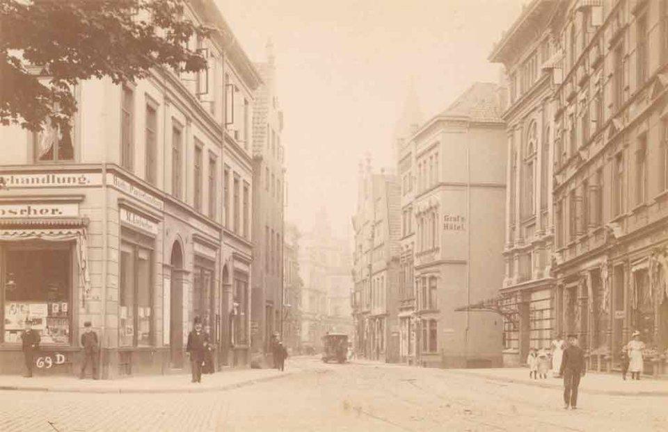 Die Schwarzweißfotografie von einer breiten Straße, die von Gebäudetrakten links und rechts gesäumt wird.