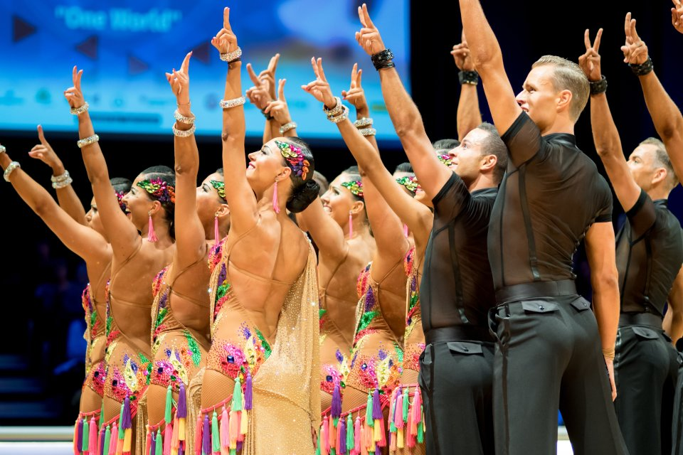 Die Schluss Pose einer Lateinformation - alle Tänzer recken Peace-Finger in die Höhe.
