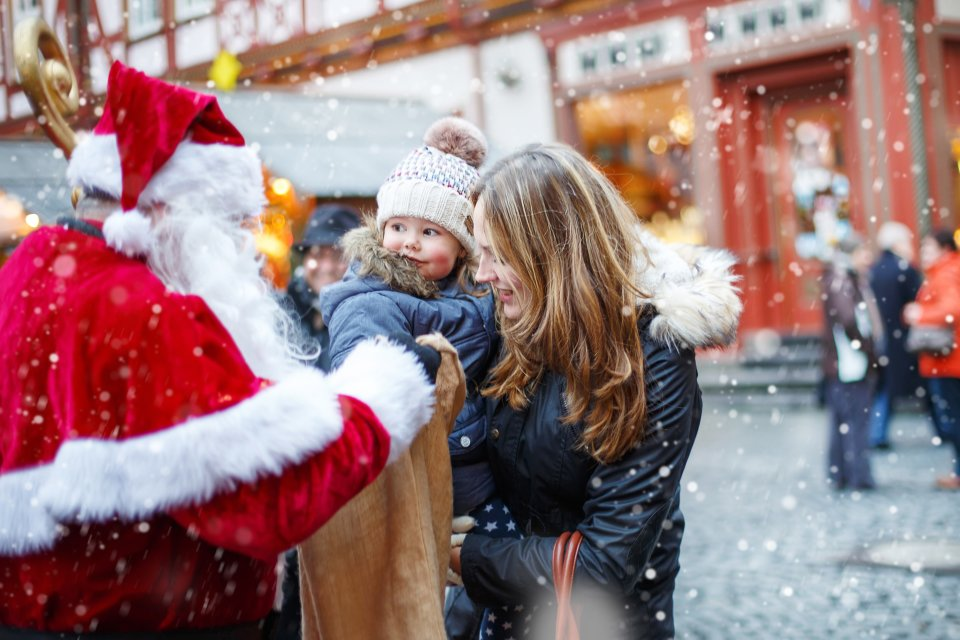 Ein Nikolaus mit einem großen Beutel beschenkt ein kleines Kind.