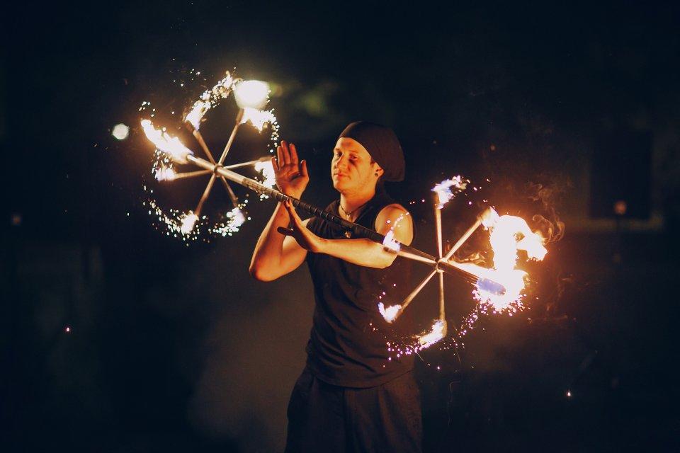 Ein Akrobat jongliert mit Feuerbällen.