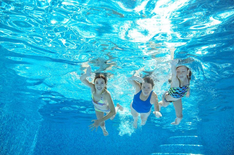 Eine Frau und zwei Mädchen aus der Unterwasserperspektive in einem Schwimmbad fotografiert. fotolia / Iuliia Sokolovska
