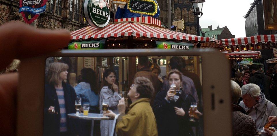 Zu sehen ist ein weißes Smartphone, auf dessen Bildschirm mehrere Personen in schwarz-weiß zu erkennen sind, die um einen kleinen Stehtisch stehen und Bier trinken. Im Hintergrund ist ein rot-weiß gestreiftes Zelt zu erkennen, auf dessen Spitze eine Figur angebracht ist. Außerdem sind im Hintergrund zwei Türme und links Teile eines Gebäudes zu sehen.