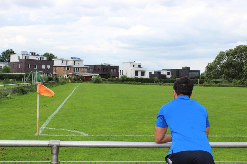 Ein Mann im blauen T-Shirt lehnt gegen den Zaun eines Fußballplatzes. Frontal ist eine grüne Wiese zu erkennen, links sind orange Fahnen zu sehen.