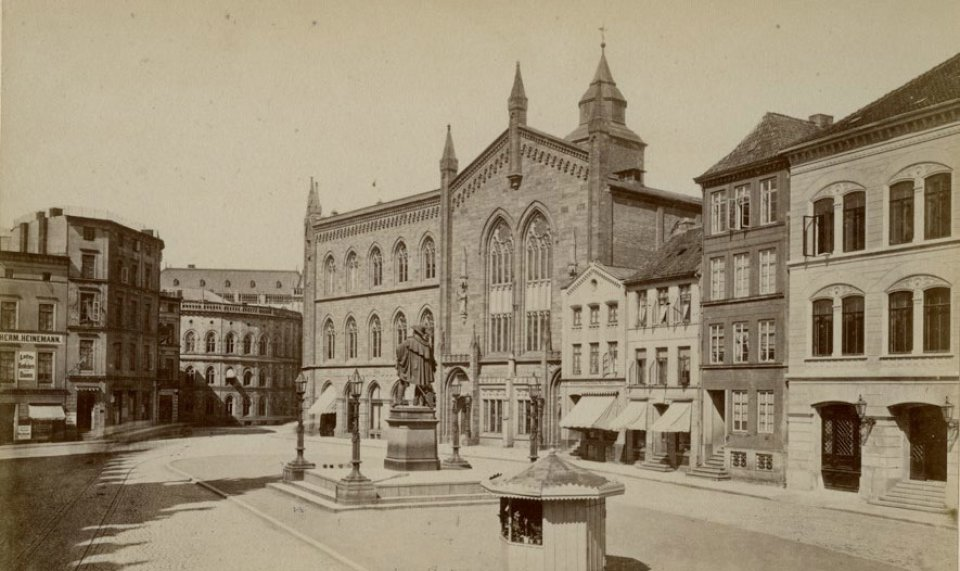 Zu sehen sind mehrere Gebäude und ein kleiner Platz, auf dem eine Statue steht. Links im Bild verlaufen Straßenbahnschienen. Die Farbe des Bildes ist hellbraun.