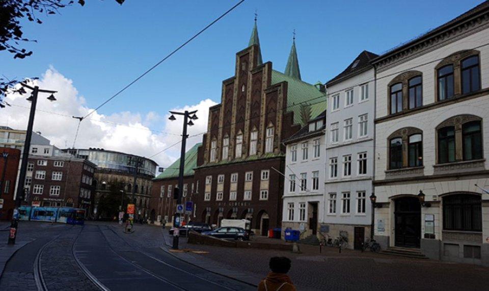 Rechts im Bild ist eine Gebäudereihe zu erkennen. Die Hälfte davon ist weiß, zwei davon sind braun und haben ein grünes Dach. Eines hat einen spitzen Giebel. Links liegen Straßenbahnschienen und im hinteren Teil fährt eine Bahn. Eine weitere Häuserreihe ist im hinteren Teil des Bildes zu erkennen.