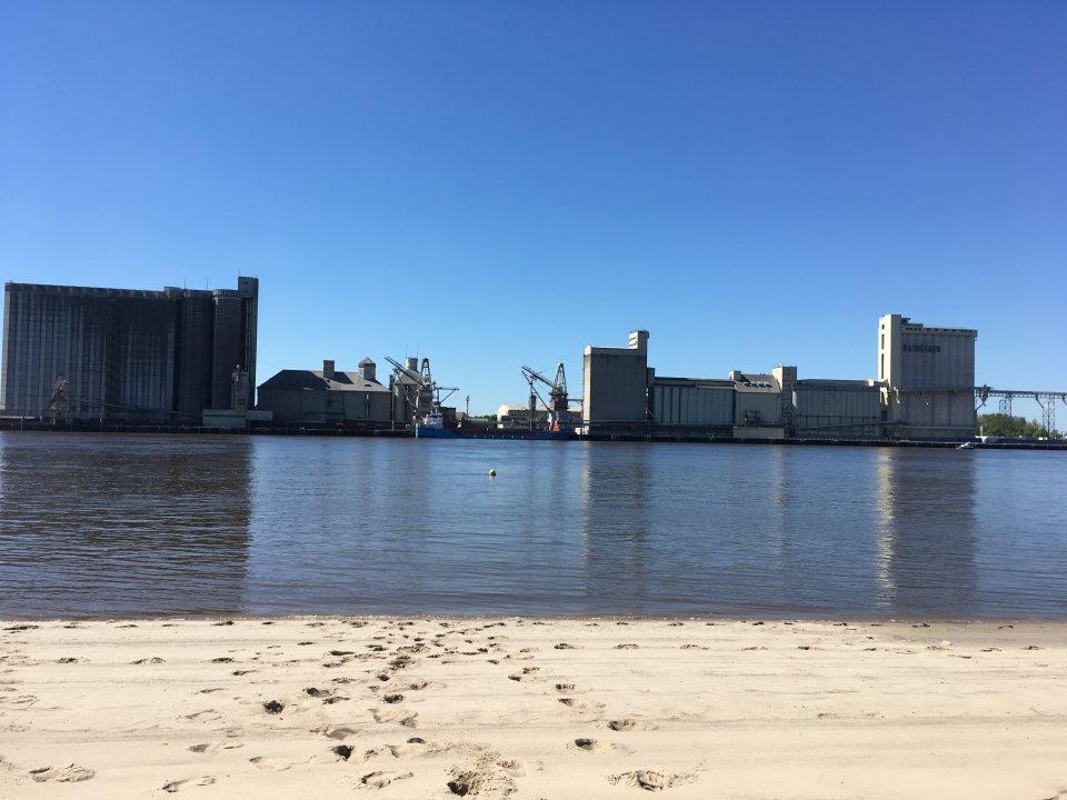 Zu sehen ist ein weißer Sandstrand mit Fußspuren, der an ein Gewässer grenzt. Auf der gegenüberliegenden Uferseite stehen große, graue Hafengebäude.
