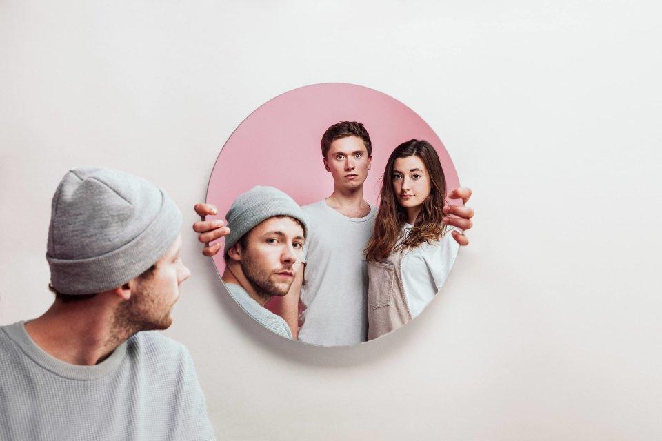 Zwei Männer und eine Frau erscheinen in einem runden Spiegel.