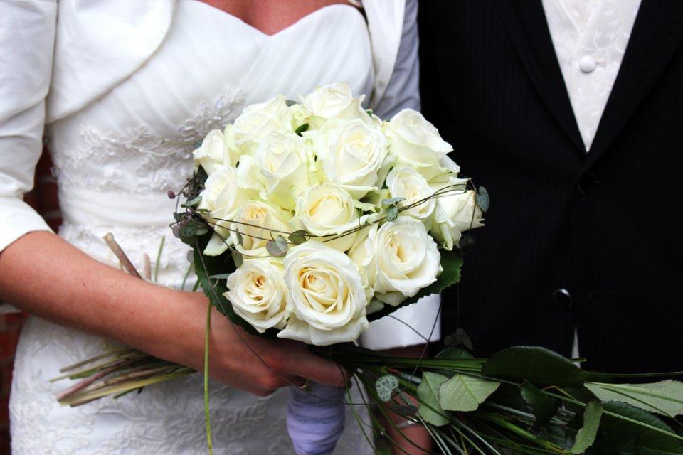Braut hält einen Brautstrauß.