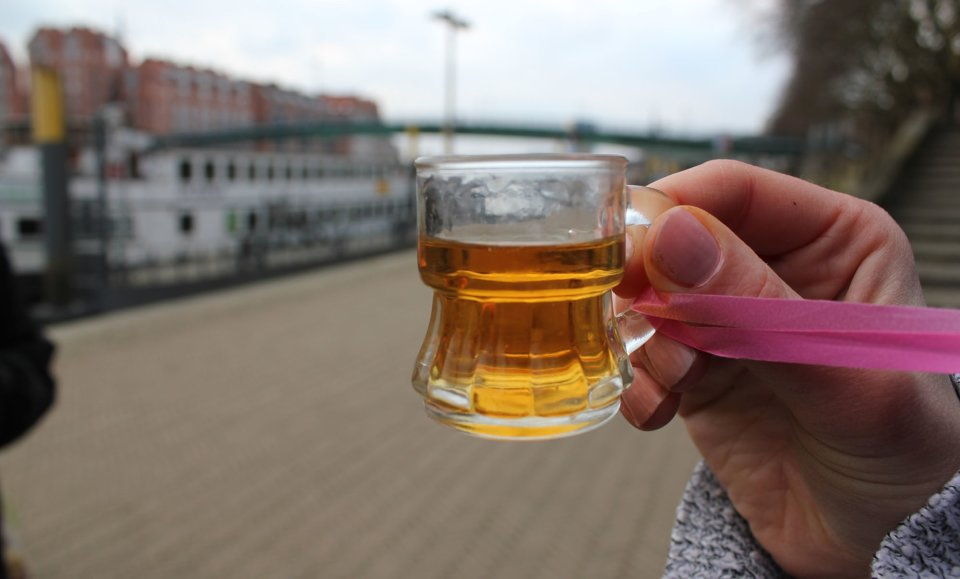 Eine Frauenhand hält ein gefülltes Schnapsglas vor die Kamera