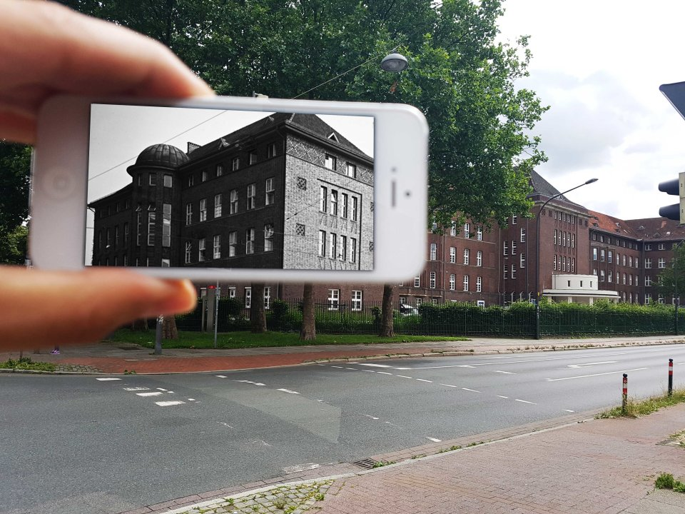 Im linken Teil des Bildes ist eine Hand zu sehen, die ein weißes Smartphone festhält- Auf dem Bildschirm ist in schwarz-weiß ein rechteckiges Gebäude mit vielen Fenstern und einem kleinen runden Turm zu erkennen. Außerhalb des Smartphones ist eine Straße zu sehen, auf dessen gegenüberliegende Seite grüne Bäume sowie ein brauner Gebäudekomplex stehen.