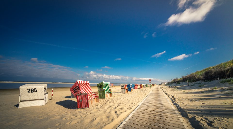Ein Holzsteg, der an einem Sandstrand entlang führt. Links vom Steg stehen bunte Strandkörbe und das Meer ist zu sehen.