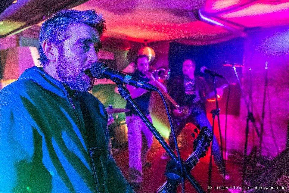 3 Männer auf der Bühne in buntem Licht