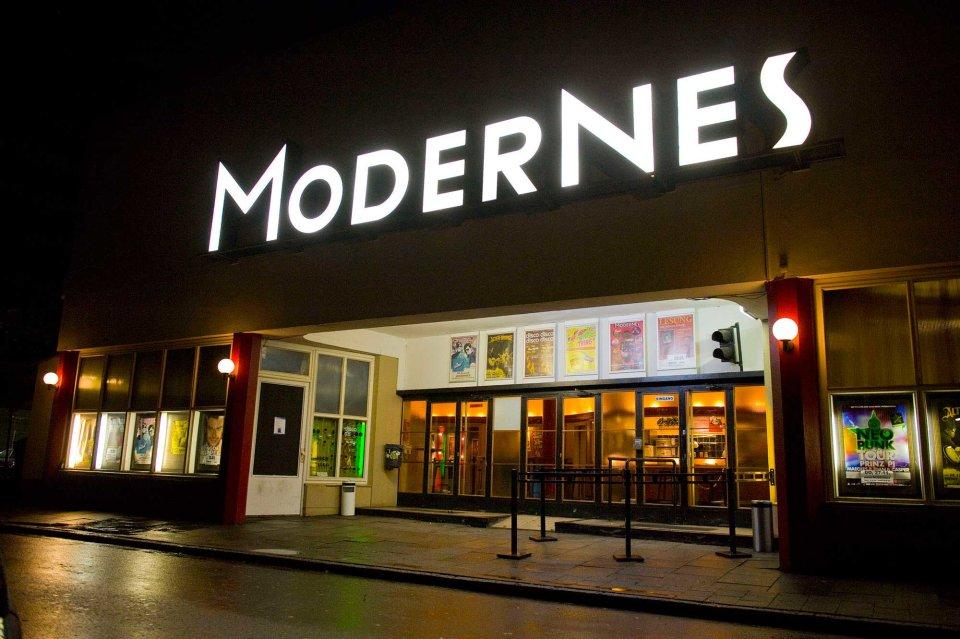 """Eine Außenaufnahme vom Modernes am Abend. Über dem Eingang leuchten die weißen Großbuchstaben """"Modernes""""."""
