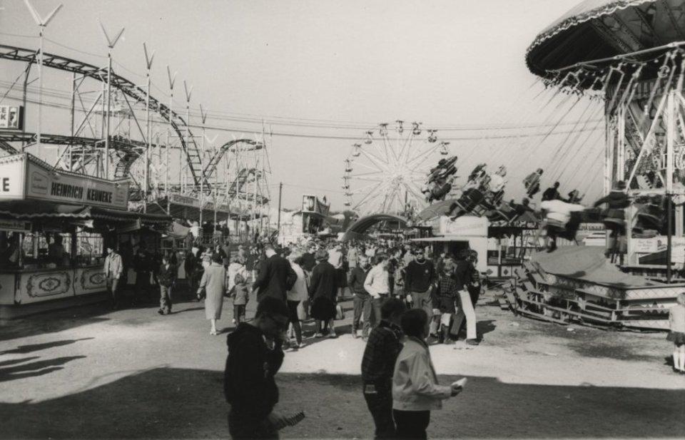 Menschen laufen einen Gang entlang, an dessen Seiten Buden und Karusselle stehen. Links ist eine Achterbahn zu erkennen, rechts ein Kettenkarussell und im Hintergrund ein Riesenrad. Das Bild ist schwarz-weiß.