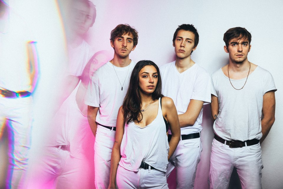 Drei Männer und eine Frau in weiß gekleidet posieren vor einer weißen Wand.
