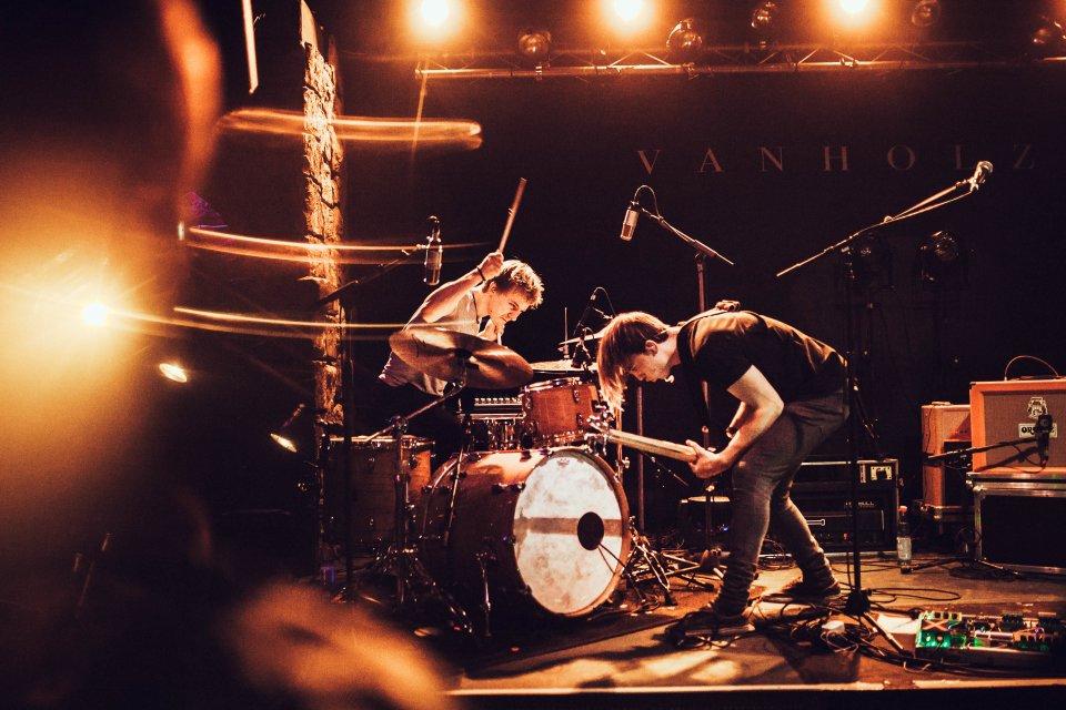 Zwei junge Männer stehen auf der Bühne und performen ein Lied.