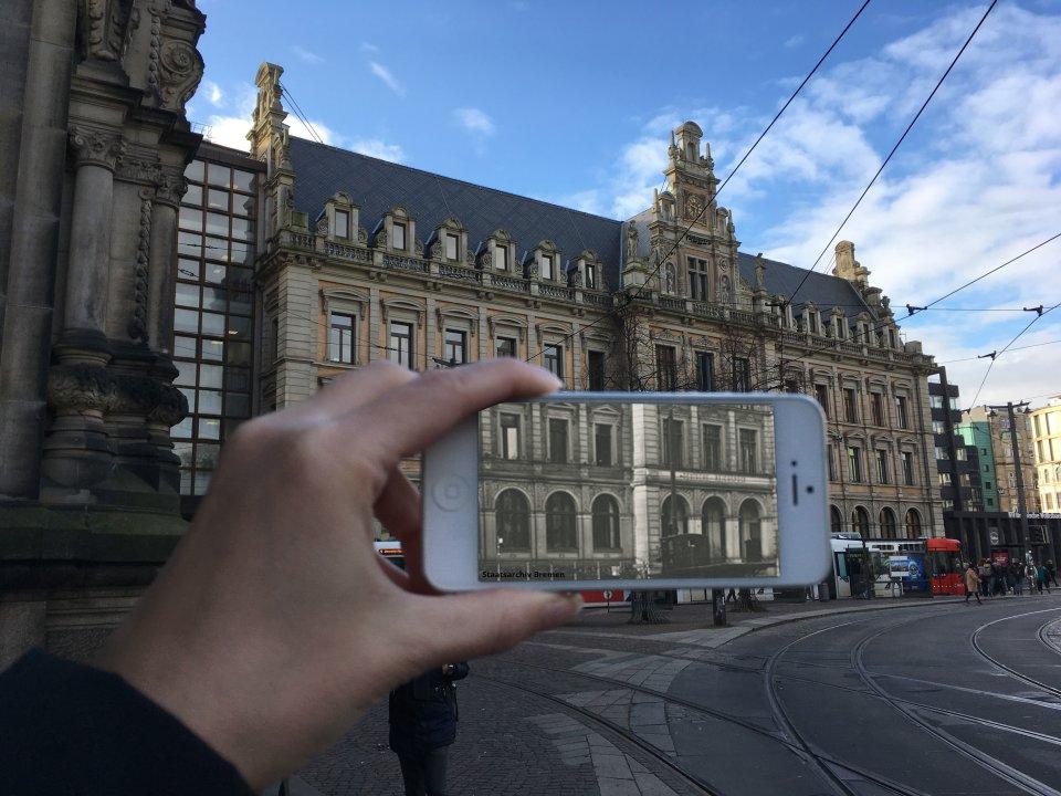 Zu sehen ist eine Hand, die ein weißes Smartphone festhält. Auf dem Bildschirm ist ein Teil einer Fensterfassade in Schwarz-Weiß zu erkennen. Im Hintergrund ist ein großes Gebäude zu erkennen mit einem verzierten Giebel.