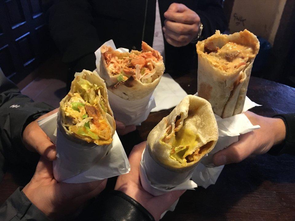 Vier Teigrollen gefüllt mit Fleisch und Salat, die von Händen ins Bild gehalten werden.