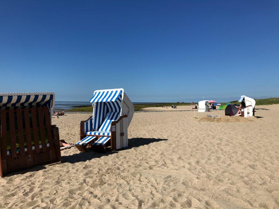 Weißer Sandstrand mit Strandkörben und blauem Himmel. Im Hintergrund sind Wiesen und das Meer zu sehen.