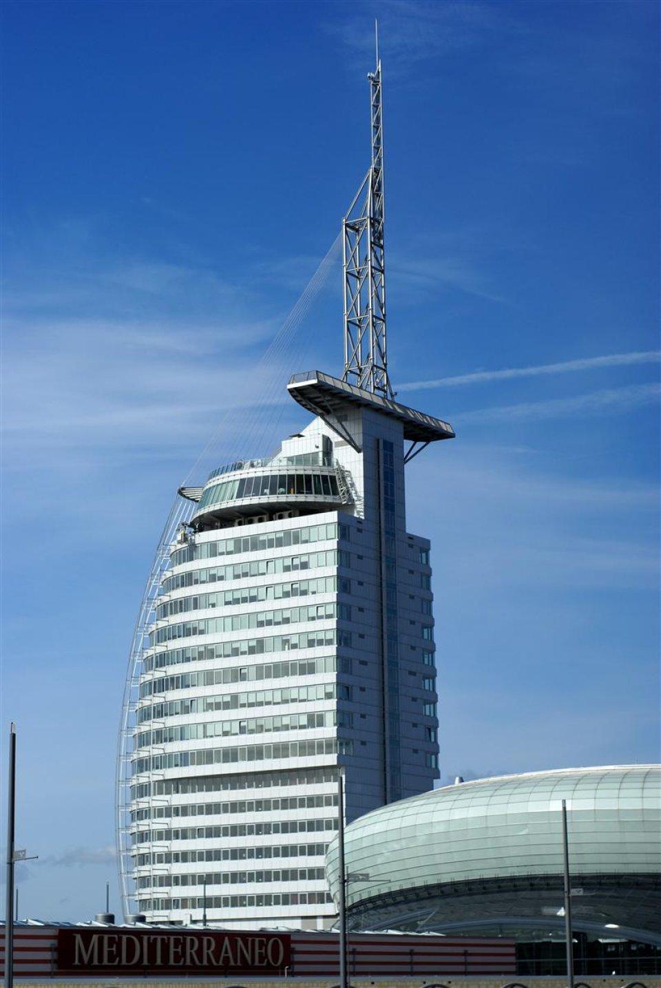 Ein mehrstöckiges Gebäude mit einer Spitze. Im Hintergrund ist blauer Himmel zu sehen.