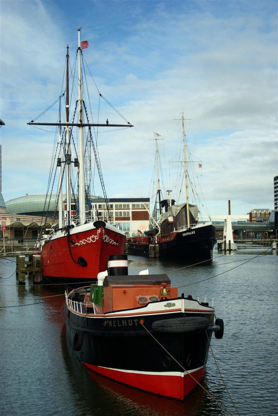 Ein kleines schwarz rotes Schiff und zwei dahinter liegende größere Schiffe mit Masten liegen in einem kleinen Hafenbecken.