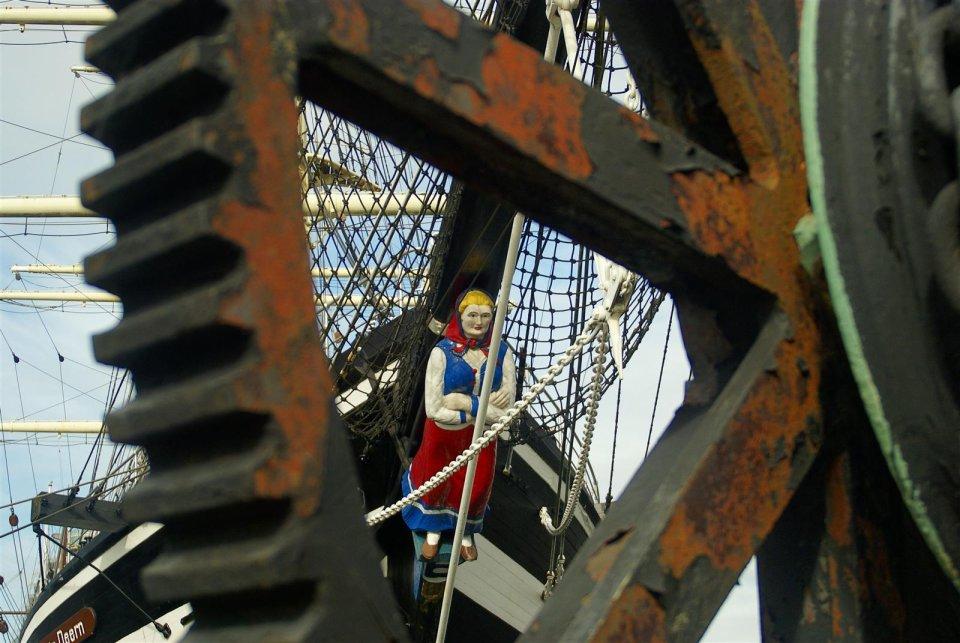 Zu sehen ist ein Teil eines zackigen, verrosteten Rades. Blickt man durch die Speiche dieses Rades ist eine Figur in Form einer Frau zu erkennen, die am vorderen Teil eines Schiffes befestigt ist.