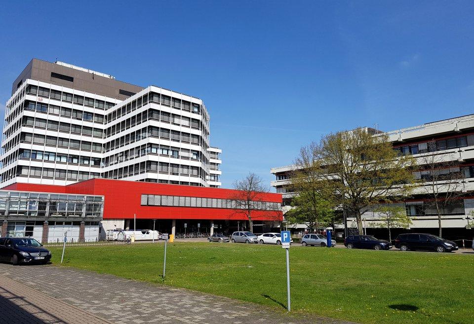 Links im Bild ist ein großes Gebäude mit Fensterreihen auf jeder Etage zu sehen. Rechts steht ein etwas kleineres Gebäude. Vor dem Gebäude ist eine grüne Wiese zu sehen, um die herum Autos parken.
