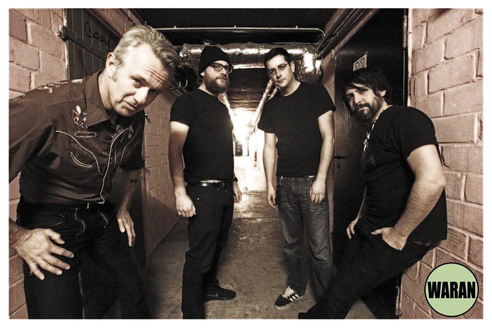 4 in schwarz gekleidete Männer stehen vor einem Gang mit Backsteinwänden. Das Bild ist in sepia.