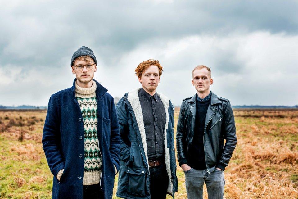 Drei junge Männer stehen mit Jacken bekleidet auf einem Feld. Im Hintergrund grauer Himmel.