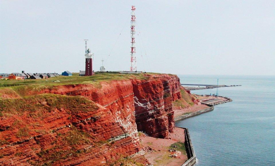 Rote Felsen bzw. Klippen an der Westseite der Insel mit bunten Häuern und einem Turm im Hintergrund. Quelle: Kurverwaltung Helgoland