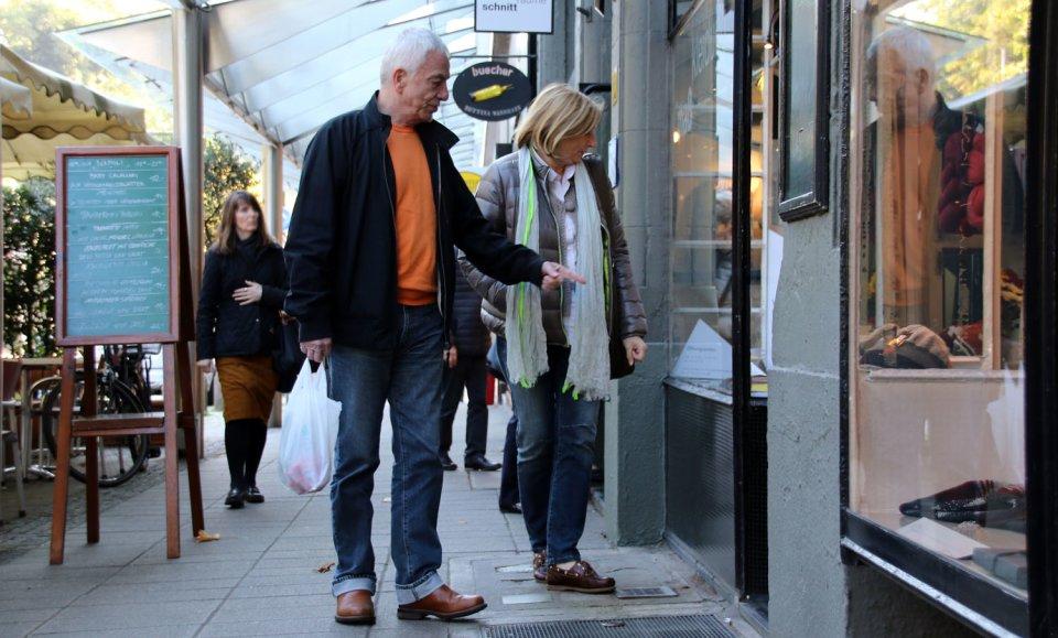 Ein Ehepaar blickt in ein Schaufenster und der Mann zeigt auf etwas in der Auslage.